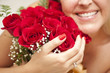 Smiling Woman Holding Bunch of Red Roses