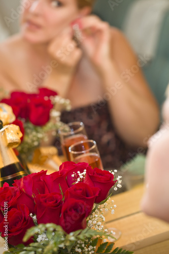 Blonde Woman Applies Makeup at Mirror Near Champagne and Roses