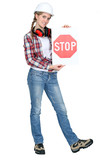 female apprentice holding stop sign