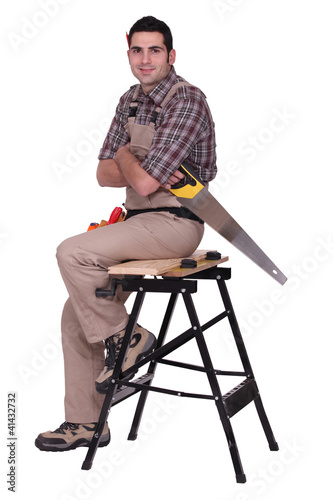 Laborer with saw sitting on a workbench