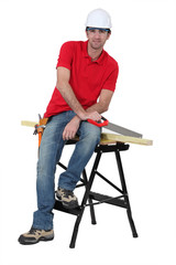 Man with a saw sitting on a workbench