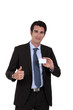 Young businessman with business card giving the thumbs-up