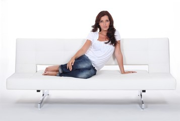 Attractive woman sitting on a modern white sofa