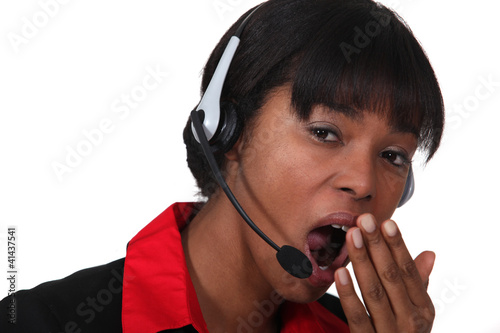 Woman with headset yawning
