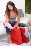 Woman sat looking through shopping bags
