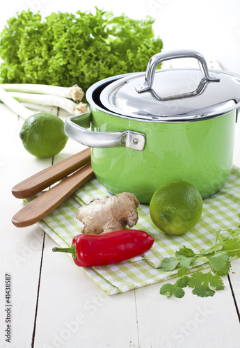 Green pot with lime, ginger, fresh coriander and chili pepper