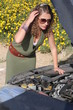 Curly blonde woman having troubles with her car