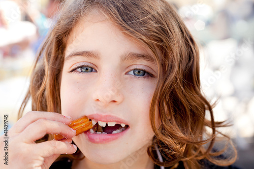 Blue eyes little girl eating churros fried crullers