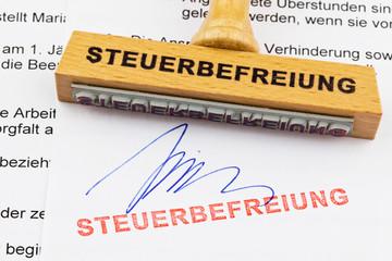 Holzstempel auf Dokument: Steuerbefreiung