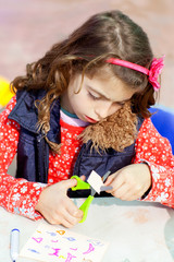 little kid girl working at school doing workshop