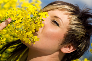 Woman smells the young Rapeseed