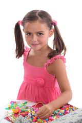 Little girl making jewelry