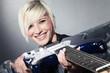 Junge rockige Frau lacht mit E-Gitarre