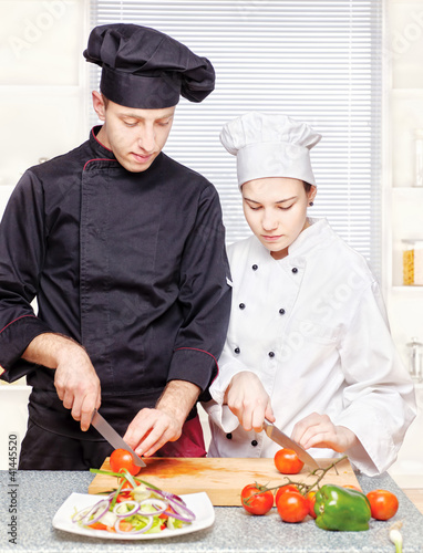 Senior chef teaches young chef to properly cut