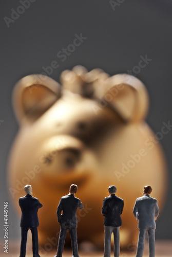 Banker vor einem goldenen Sparschwein