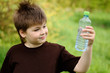 A boy with a bottle of water in nature