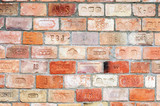 Old wall made of bricks stamped with different brickyards' names