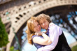 Vacation in Paris. Young romantic couple hugging under the Eiffe