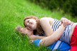 Romantic couple lying on the grass and hugging