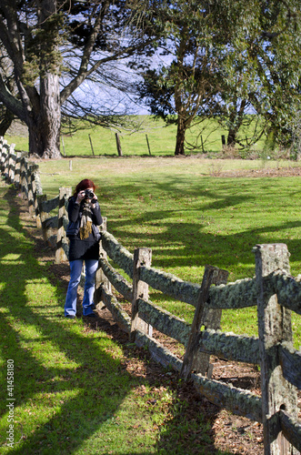 Female photographer at old post and rail fence