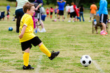 Young boy playing soccer during organized league game