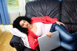 Sleeping woman holding laptop lying on a sofa