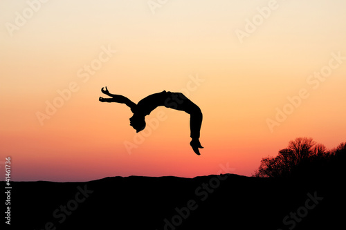 Leinwandbild Motiv silhouette of gymnast doing a backflip in sunset