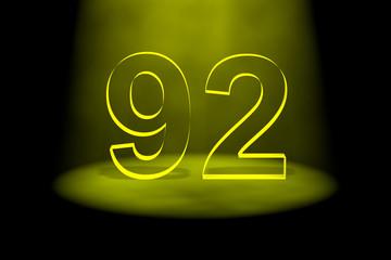 Number 92 illuminated with yellow light