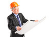 A mature construction worker with helmet holding blueprint