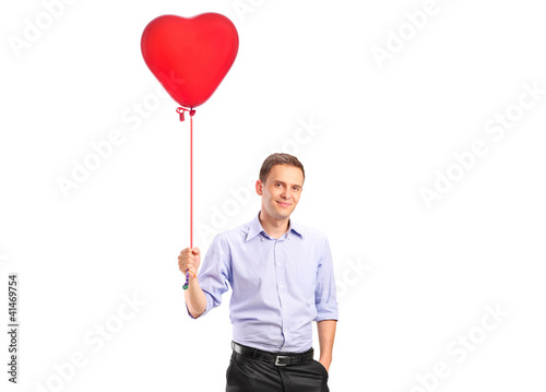 A smiling young male holding a red heart shaped balloon