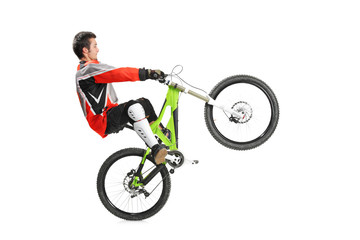 Young biker with his mountain bike jumping