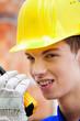 Lehrling / Azubi. Bauarbeiter auf Baustelle mit He