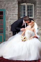 beautiful groom and bride kissing in old interior