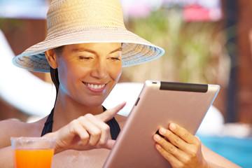 Frau mit Tablet-Computer am Pool
