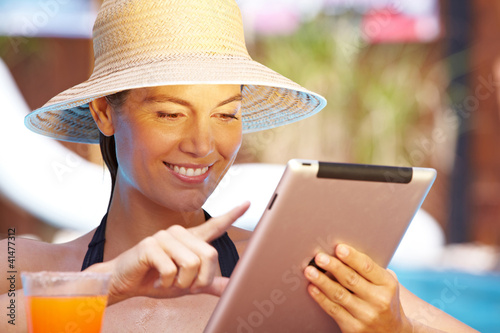 Frau mit Tablet-Computer am Pool