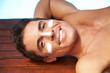 Lachender Mann mit Sonnencreme
