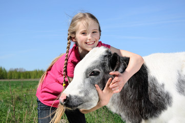 little girl petting a beautiful calf