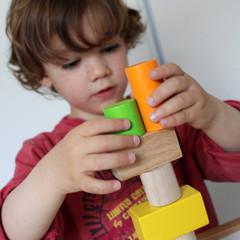 enfant qui empile des formes en bois