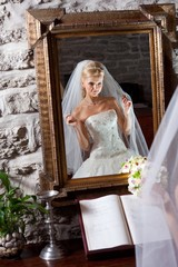 beautiful bride in white in front of mirror