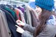 Leinwanddruck Bild - Woman choosing clothes at the flea market.
