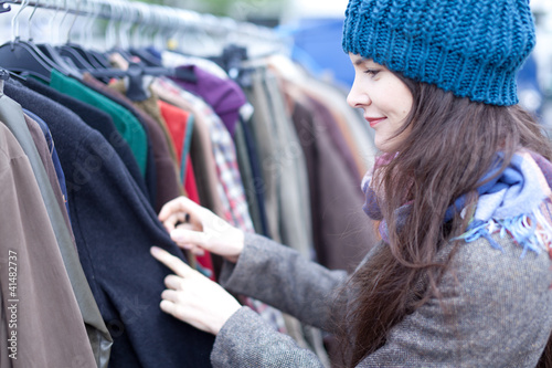 Woman choosing clothes at the flea market.