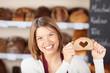 Leinwanddruck Bild - verkäuferin mit herz-brot in der bäckerei