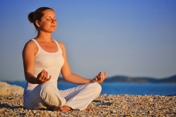 Young woman during yoga meditation on the beach