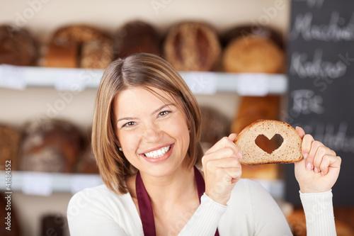 Leinwanddruck Bild verkäuferin mit herz-brot in der bäckerei