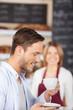 lächelnder mann trinkt kaffee in der bäckerei