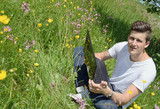 Young business man in nature workstation on meadow poster
