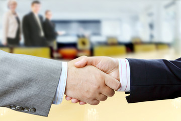 Closeup of businessmen and businesswoman shaking hands