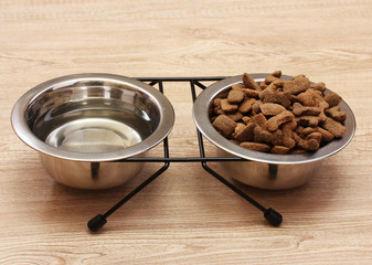 dry dog food and water in metal bowls on wooden background