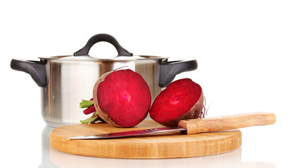 Young red beet on wooden board and pan isolated on white