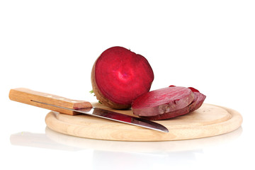 Young red beet and knife on wooden board isolated on white